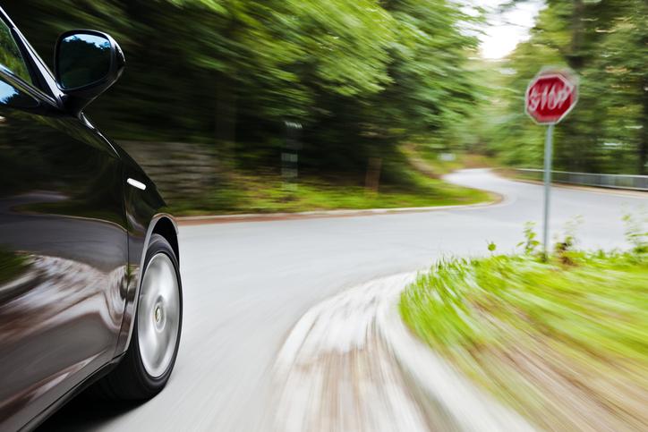 blurry image of a car speeding around a corner through a stop sign
